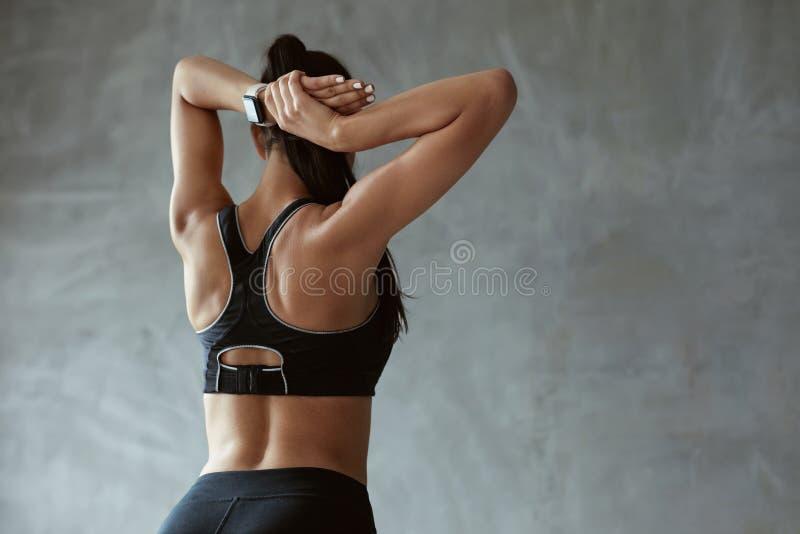 Mulher dos esportes no Sportswear da forma que esticam para trás e nos ombros fotos de stock