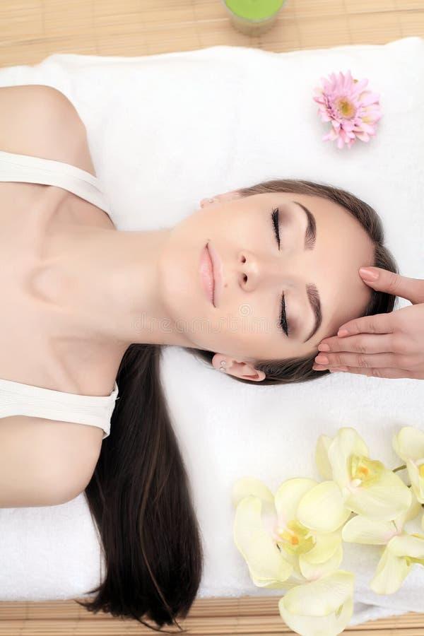 Mulher dos termas Jovem mulher bonita que obtém um tratamento da cara no salão de beleza Massagem de cara imagem de stock