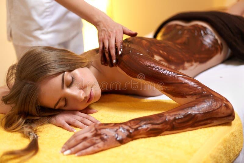 Mulher dos termas A jovem mulher obtém a máscara do corpo do chocolate no salão de beleza fotografia de stock royalty free