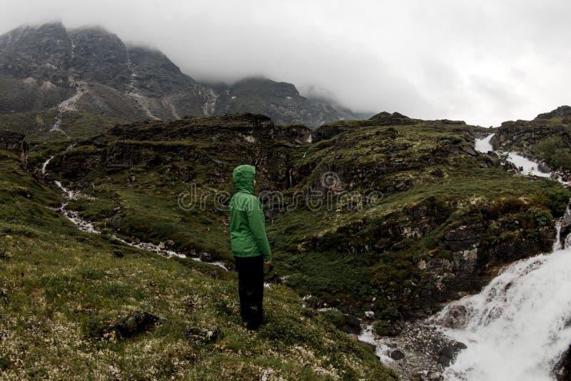 Mulher dos turistas que estão pelo rio da montanha em um dia de verão nevoento na chuva fotos de stock royalty free