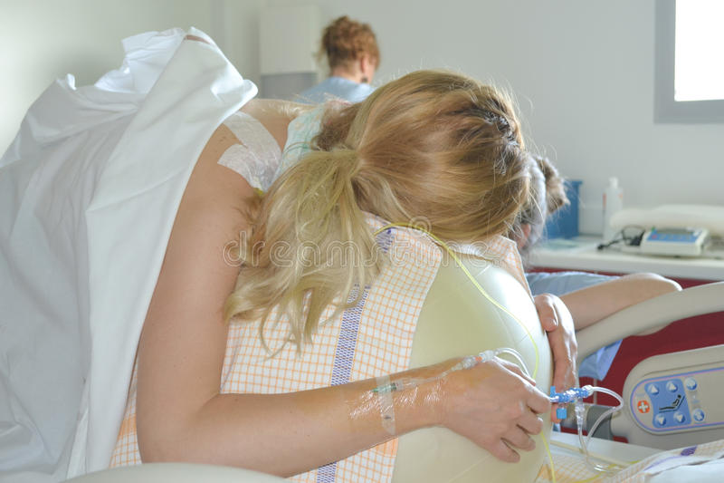 Mulher durante contrações em um parto da bola da aptidão imagens de stock