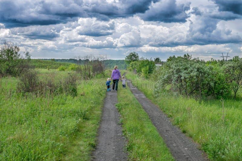 A mulher e as crianças andam na estrada sob nuvens escuras fotografia de stock royalty free