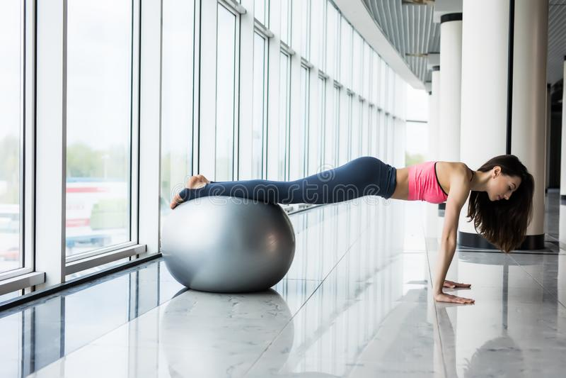 Mulher e bola da aptidão Jovem mulher que faz exercícios com a bola do ajuste no gym A mulher está fazendo a aptidão em casa no a foto de stock
