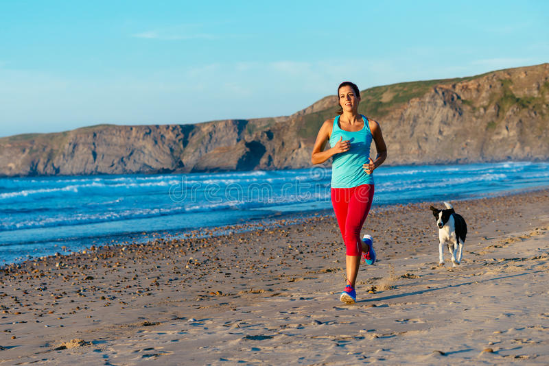 Mulher e cão da aptidão que correm na praia imagens de stock royalty free