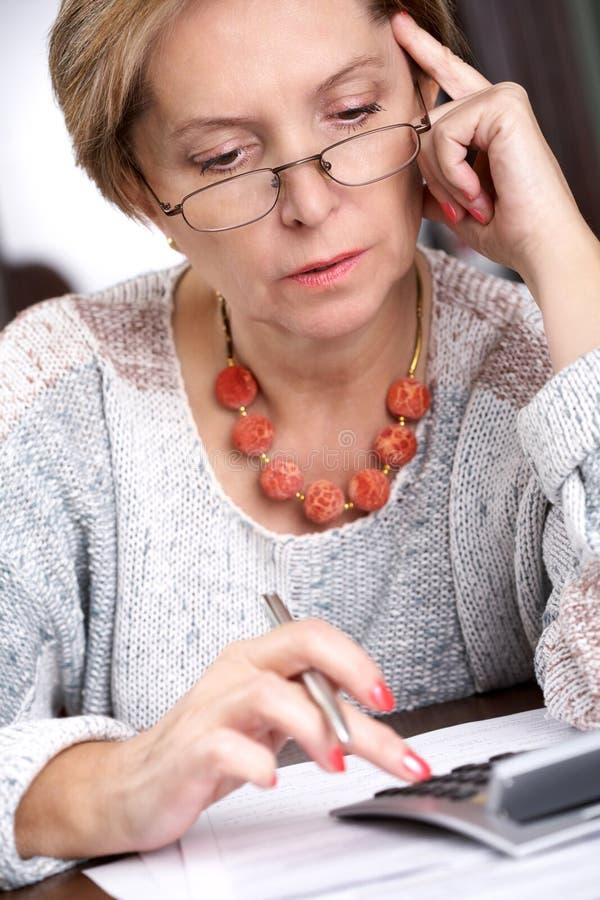 Mulher e calculadora maduras foto de stock royalty free
