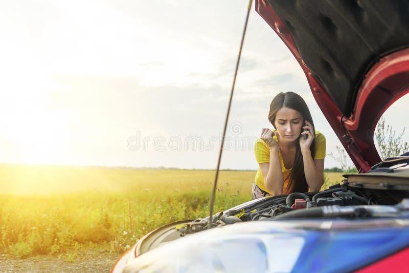 Mulher e carro quebrado foto de stock