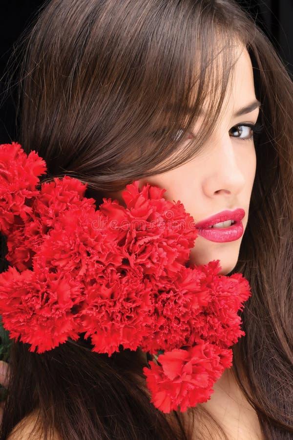 Mulher e cravos vermelhos fotografia de stock