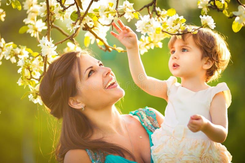 A mulher e a criança felizes na mola de florescência jardinam. Kissi da criança imagem de stock