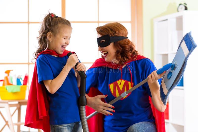 A mulher e a criança felizes preparam-se para a limpeza da sala Mãe e sua menina da criança que jogam junto Família em trajes do  imagem de stock royalty free