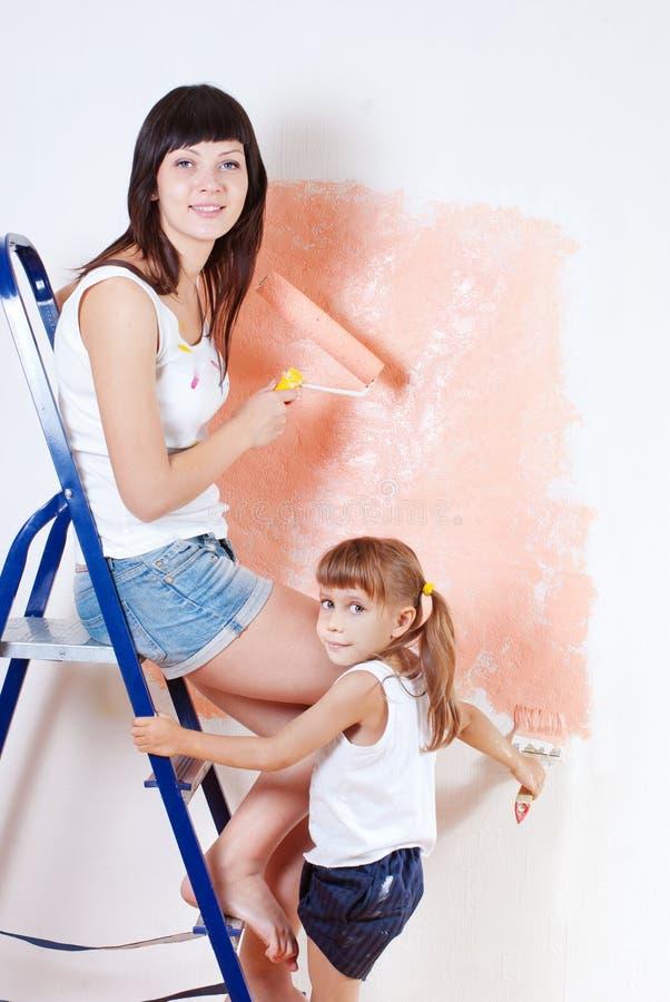 A mulher e a criança pintam a parede fotografia de stock royalty free