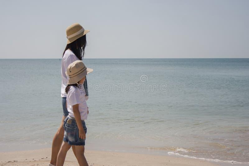A mulher e a criança que andam na praia da areia e que sentem relaxam com opinião do seascape no fundo imagens de stock royalty free