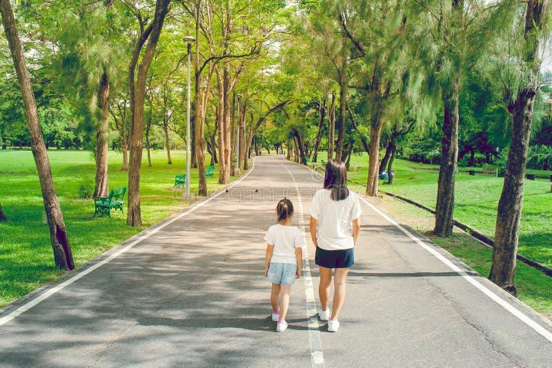 Mulher e criança que andam no passeio e na passagem no parque público fotos de stock royalty free