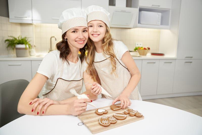 Mulher e criança que decoram as cookies do gengibre, levantando foto de stock royalty free
