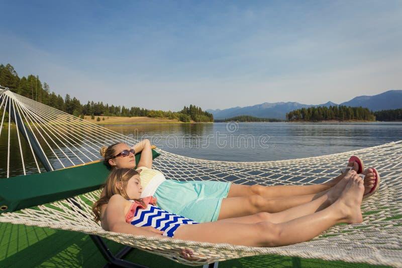 Mulher e criança que relaxam em uma rede em um lago bonito mountain imagens de stock royalty free