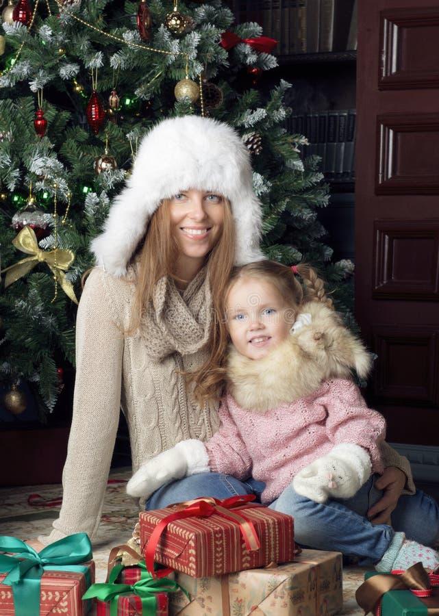 Mulher e criança que sentam-se perto da árvore de Natal foto de stock royalty free