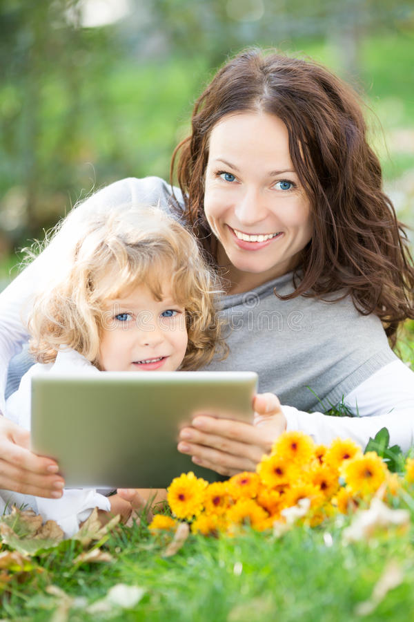 Mulher e criança que usa o PC da tabuleta fora fotografia de stock