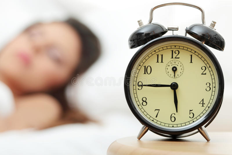Mulher e despertador caucasianos bonitos imagens de stock
