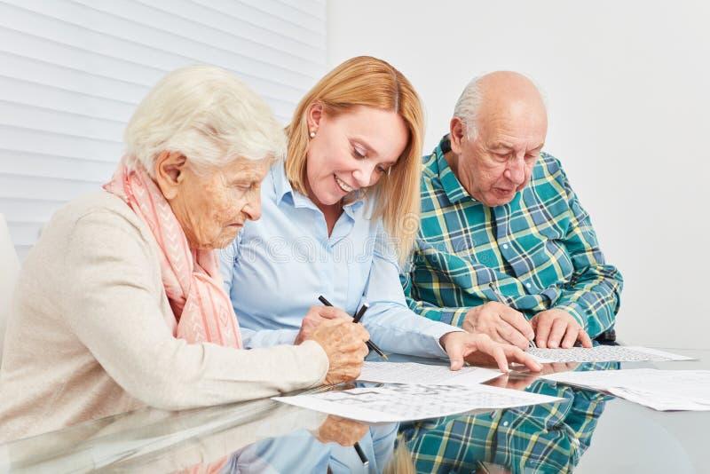A mulher e dois sêniores estão fazendo o treinamento da memória foto de stock
