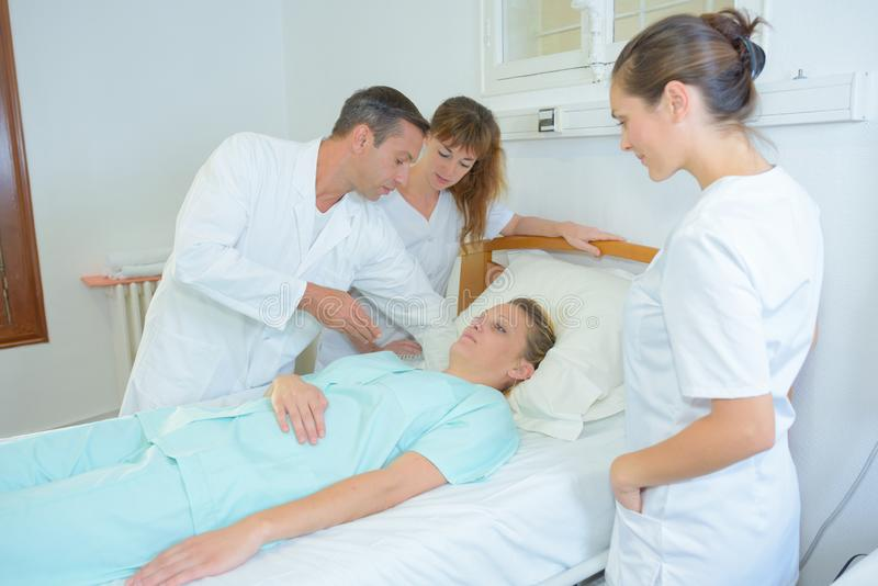 Mulher e doutores com na divisão de hospital fotografia de stock