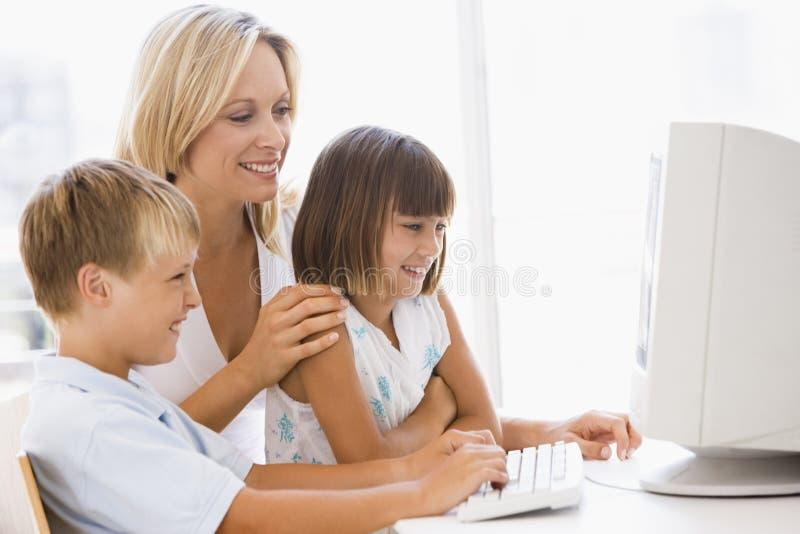 Mulher e duas crianças novas com computador imagem de stock