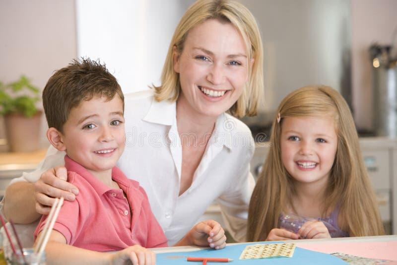 Mulher e duas crianças novas na cozinha com arte p fotografia de stock