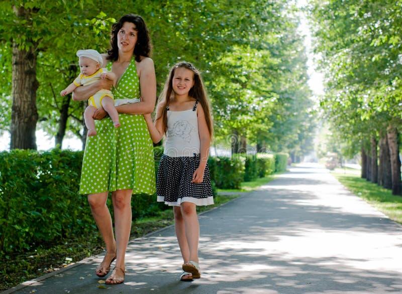 Mulher e duas crianças que andam abaixo da avenida imagem de stock