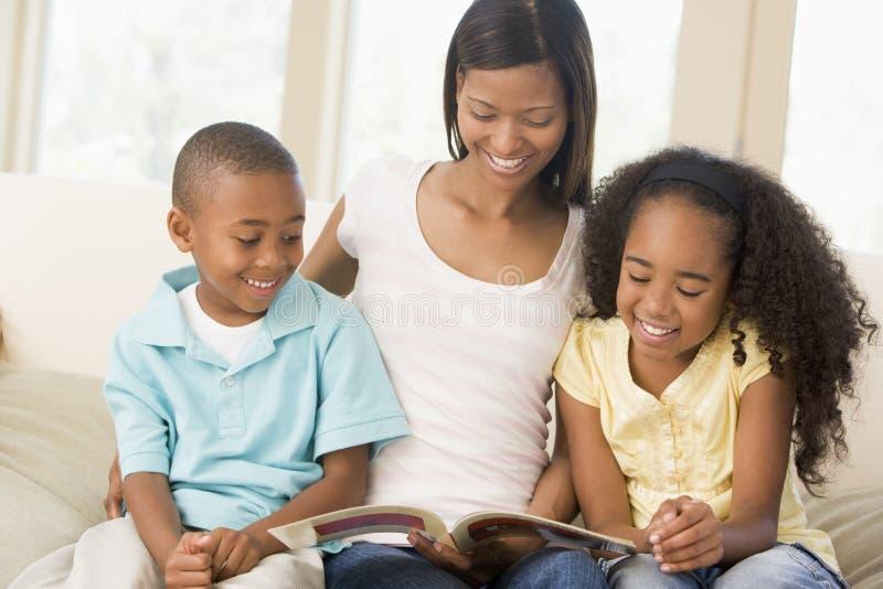 Mulher e duas crianças que sentam-se na sala de visitas fotografia de stock royalty free