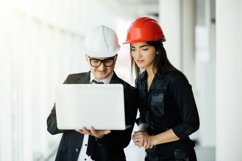 Mulher e empresário e arquiteto do homem no hemlet na reunião de negócios, olhando o portátil em planos da construção foto de stock