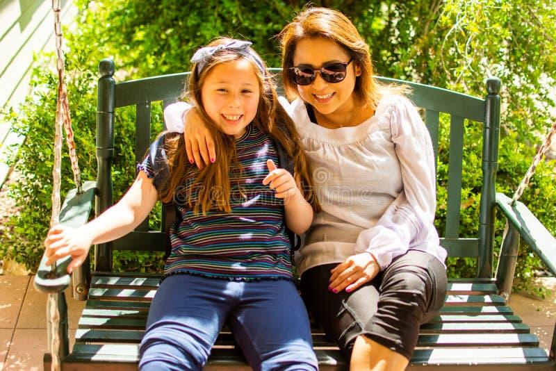 Mulher e filha de Latina que sentam-se junto em um balanço na máscara fotos de stock royalty free