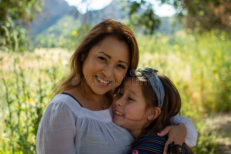 Mulher e filha de Latina que sorriem junto na frente de um campo brilhante em um parque fotografia de stock royalty free