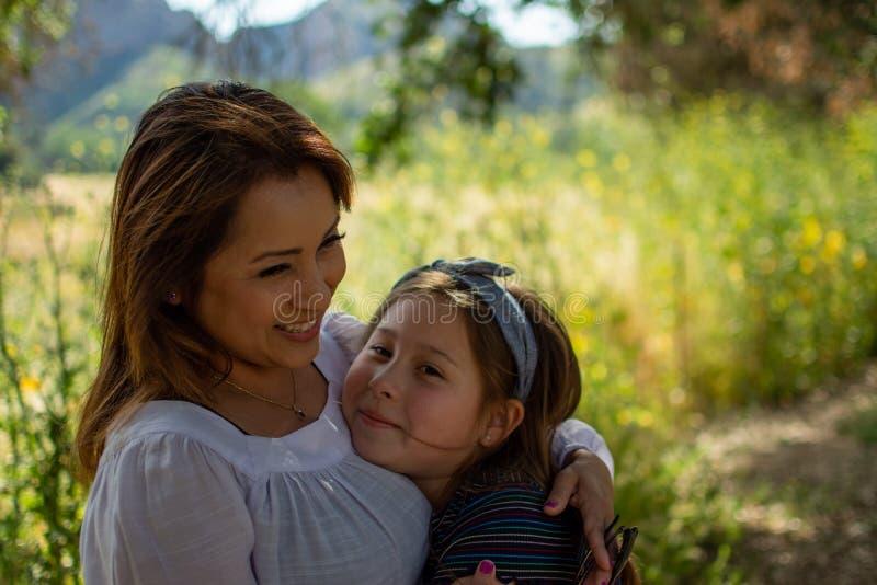 Mulher e filha de Latina que sorriem junto na frente de um campo brilhante em um parque imagens de stock