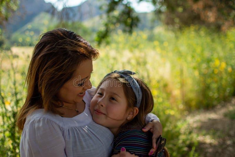 Mulher e filha de Latina que sorriem junto na frente de um campo brilhante em um parque imagem de stock royalty free