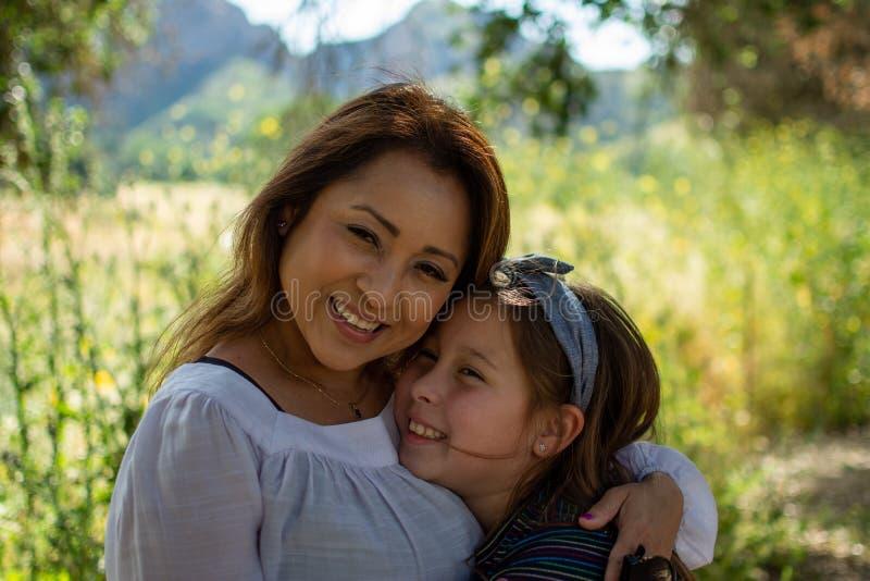 Mulher e filha de Latina que sorriem junto na frente de um campo brilhante em um parque foto de stock