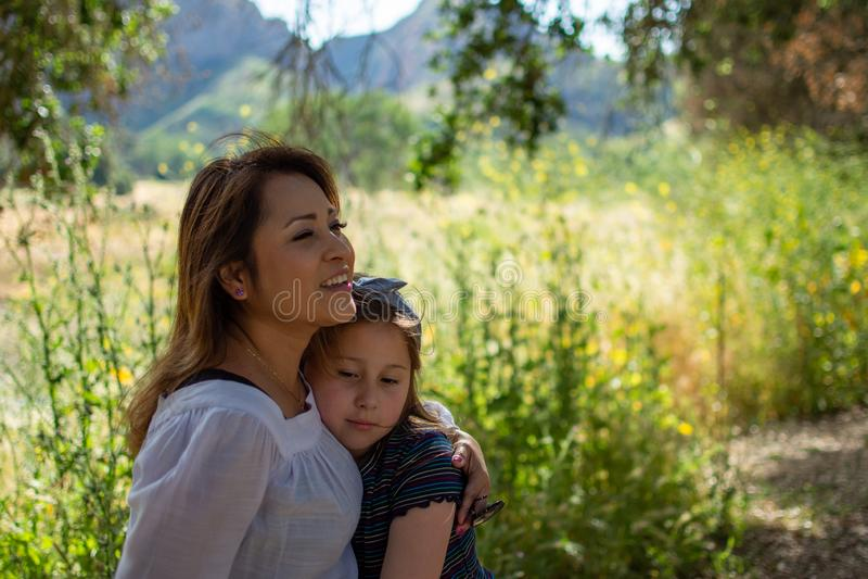 Mulher e filha de Latina que sorriem junto na frente de um campo brilhante em um parque imagem de stock