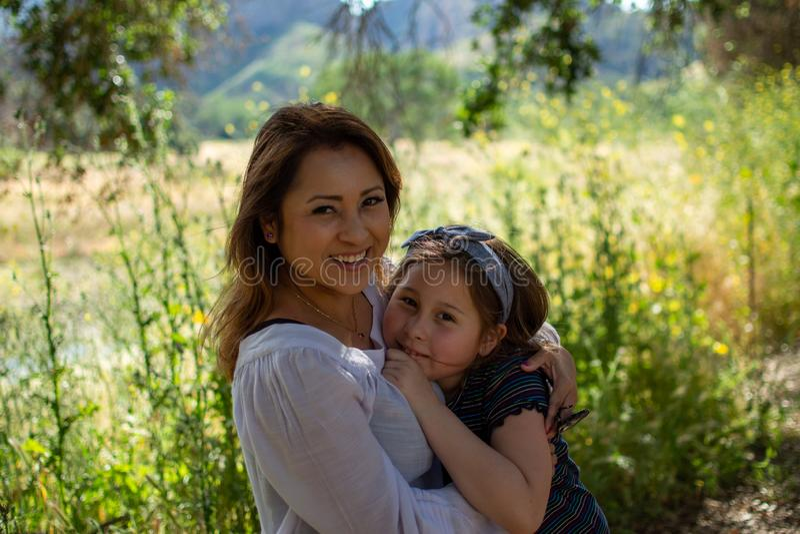 Mulher e filha de Latina que sorriem junto na frente de um campo brilhante em um parque fotos de stock royalty free