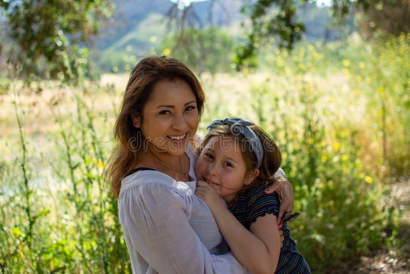 Mulher e filha de Latina que sorriem junto na frente de um campo brilhante em um parque imagens de stock royalty free