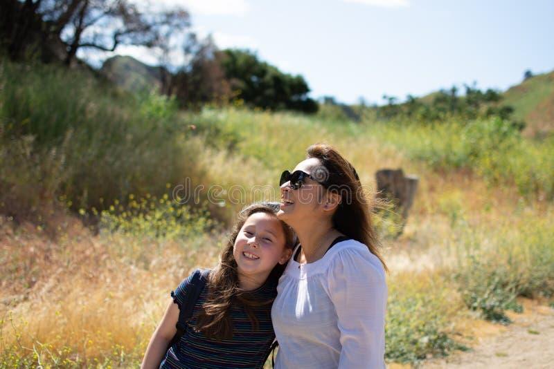 Mulher e filha que andam junto em uma fuga ou em uma estrada de terra nas madeiras ao lado de um campo amarelo fotos de stock royalty free