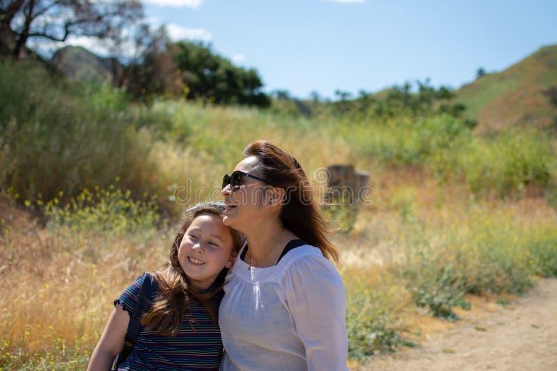 Mulher e filha que andam junto em uma fuga ou em uma estrada de terra nas madeiras ao lado de um campo amarelo imagens de stock