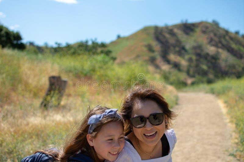 Mulher e filha que andam junto em uma fuga ou em uma estrada de terra nas madeiras ao lado de um campo amarelo imagem de stock royalty free