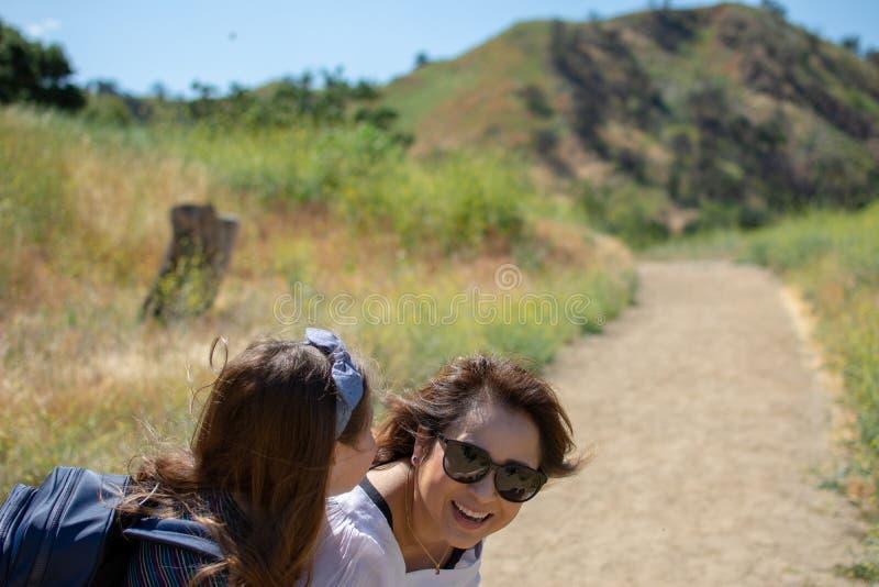 Mulher e filha que andam junto em uma fuga ou em uma estrada de terra nas madeiras ao lado de um campo amarelo fotos de stock