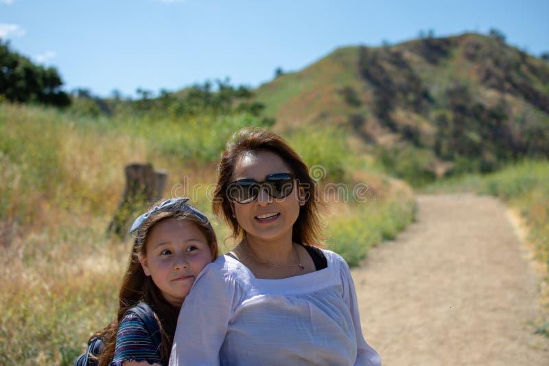 Mulher e filha que andam junto em uma fuga ou em uma estrada de terra nas madeiras ao lado de um campo amarelo fotografia de stock