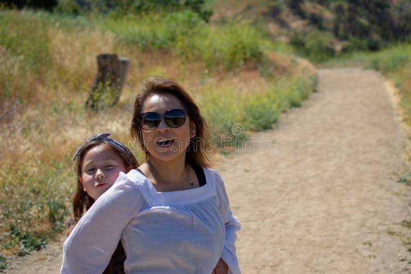 Mulher e filha que andam junto em uma fuga ou em uma estrada de terra nas madeiras ao lado de um campo amarelo foto de stock