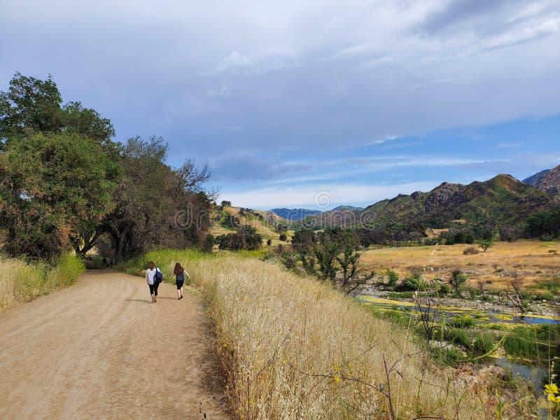 Mulher e filha que andam junto em uma fuga ou em uma estrada de terra nas madeiras ao lado de um campo amarelo foto de stock royalty free