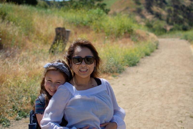 Mulher e filha que estão e que riem junto ao jogar em um córrego ou em um rio fotos de stock royalty free