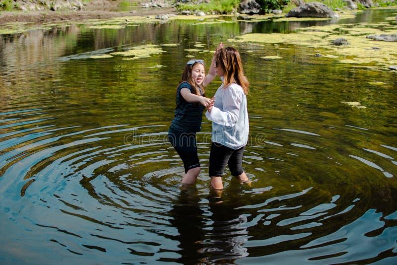 Mulher e filha que est?o e que riem junto ao jogar em um c?rrego ou em um rio imagem de stock