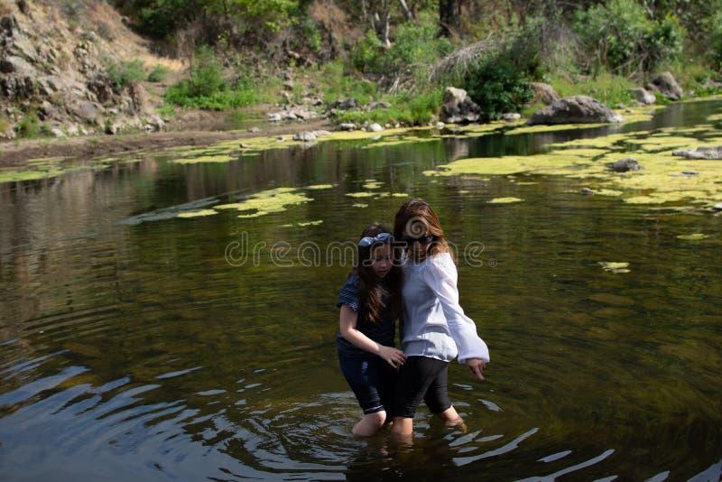 Mulher e filha que est?o e que riem junto ao jogar em um c?rrego ou em um rio fotografia de stock