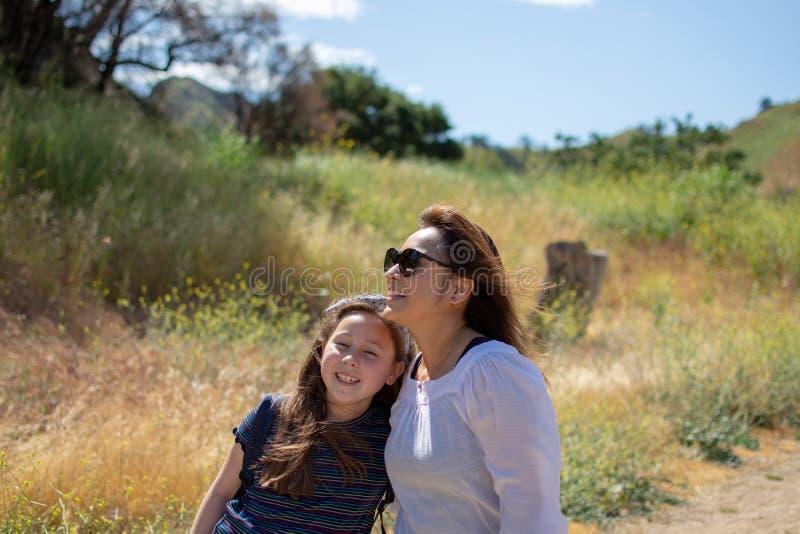 Mulher e filha que est?o e que riem junto ao jogar em um c?rrego ou em um rio foto de stock royalty free