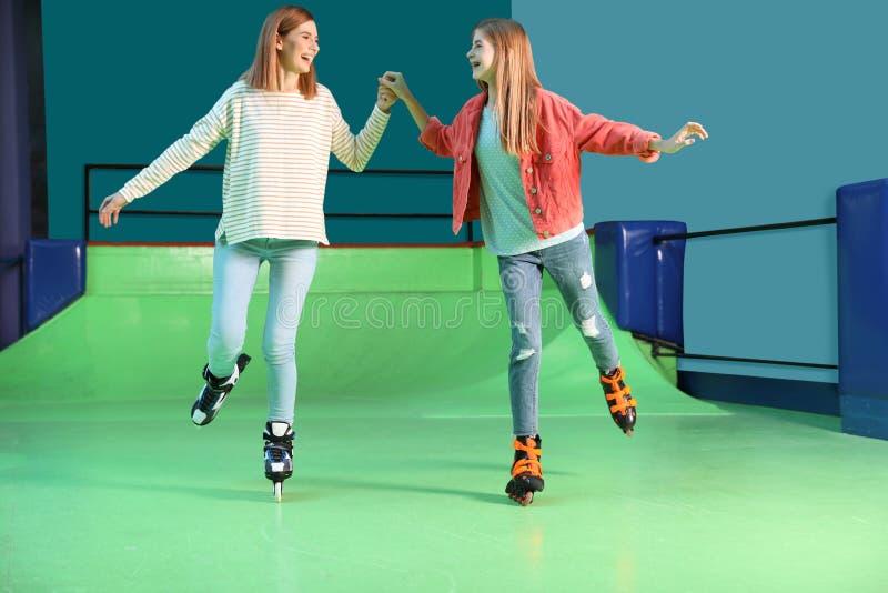 Mulher e filha que têm o divertimento na pista de patinagem do rolo fotografia de stock royalty free