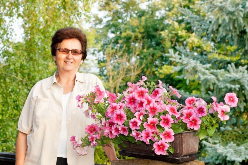 Mulher e flores sênior fotografia de stock royalty free
