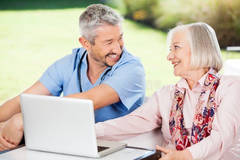 Mulher e guarda superiores felizes com portátil sobre fotos de stock